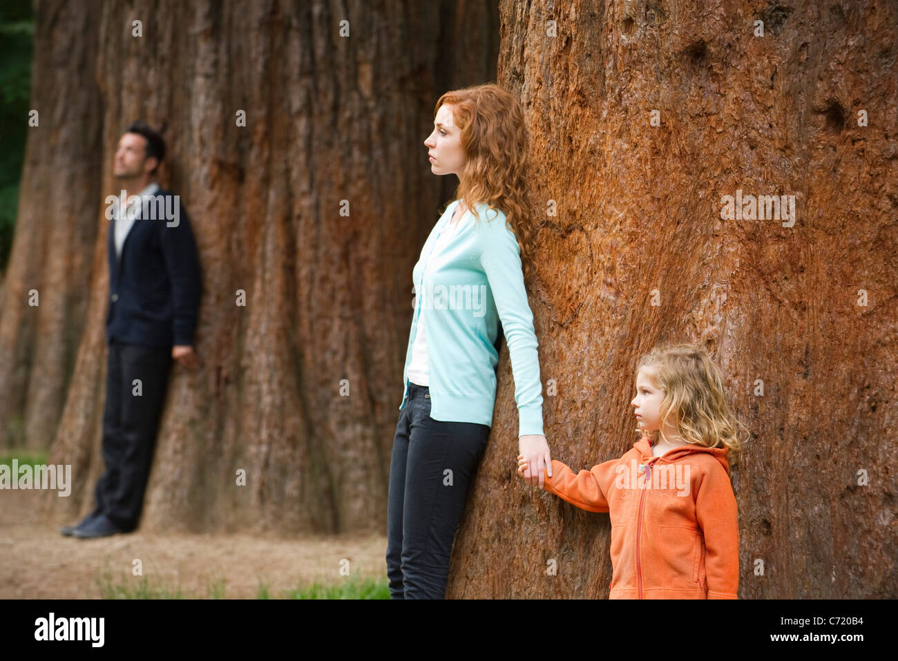 Mother and daughter leaning against tree, father standing separate in background - Stock Image