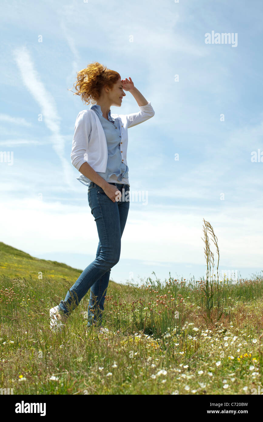 Woman walking in meadow, shading eyes with hand - Stock Image