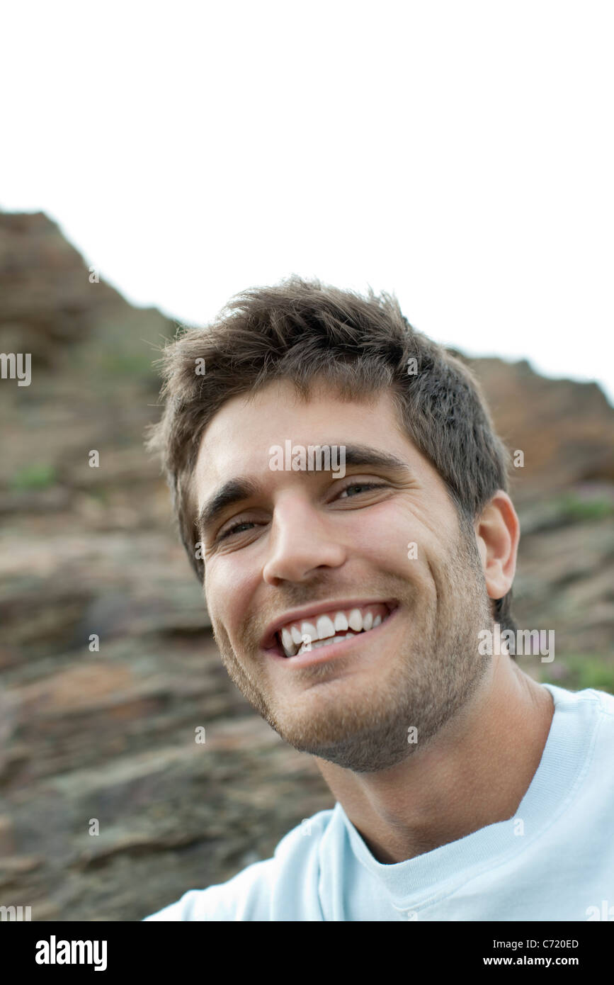 Young man laughing outdoors, portrait - Stock Image