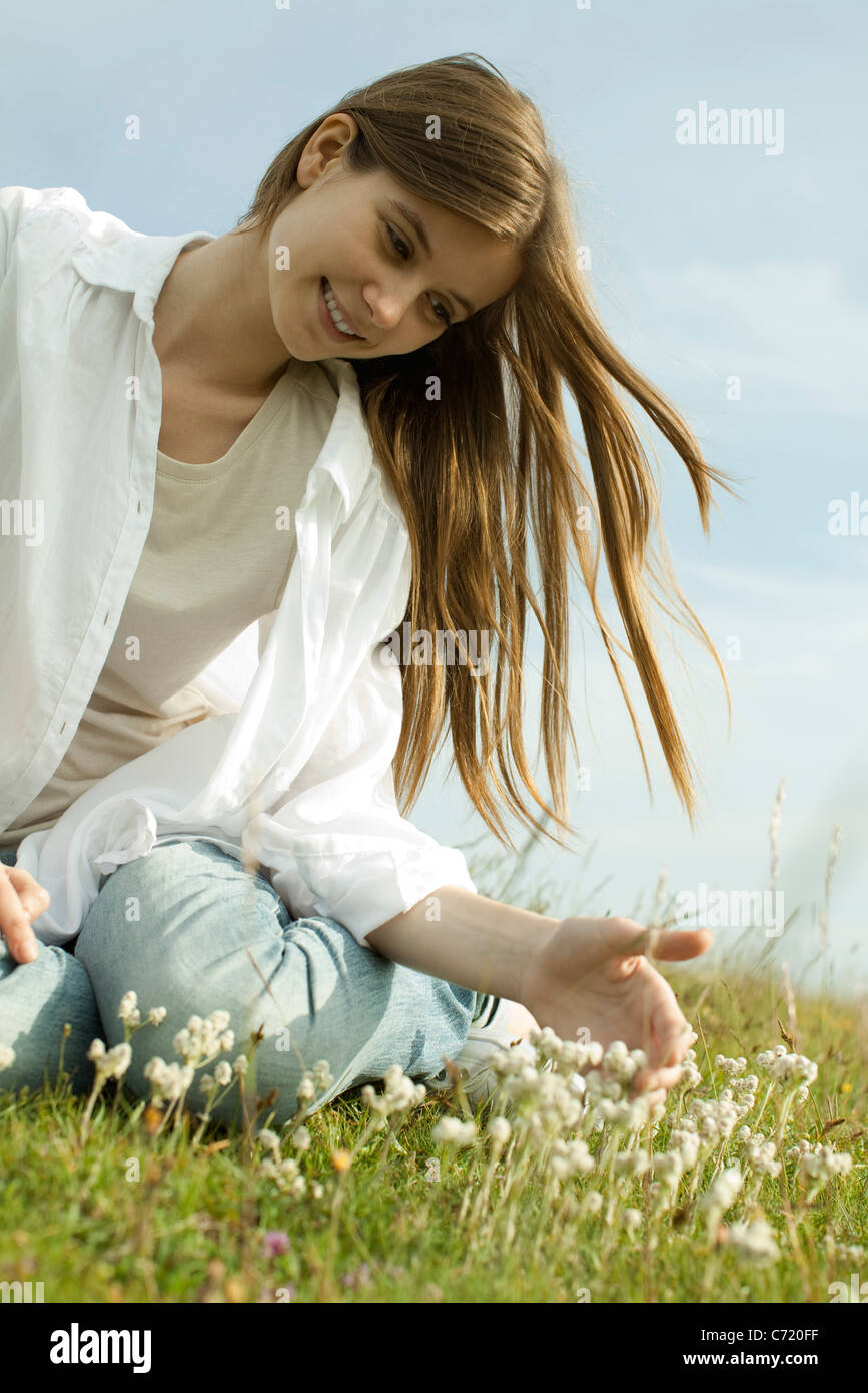 Young woman sitting on meadow with wildflowers - Stock Image