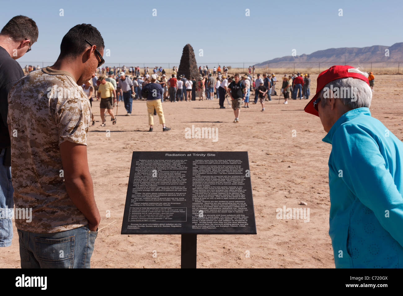 Sightseers read a sign at Trinity Site describing radiation at the the site of the world's first atomic bomb - Stock Image