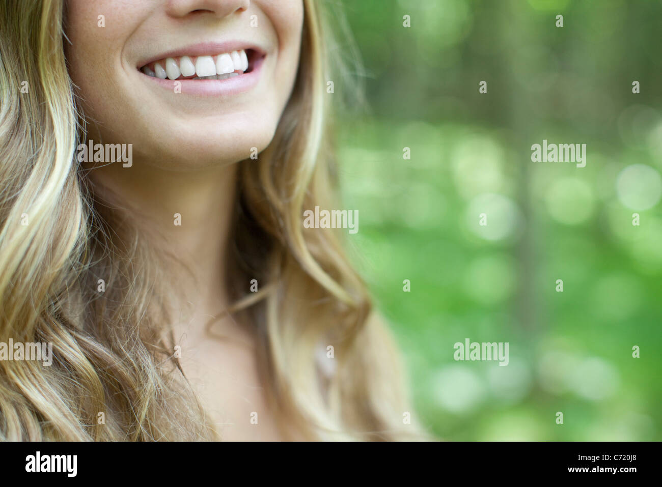 Young woman with toothy smile, cropped - Stock Image