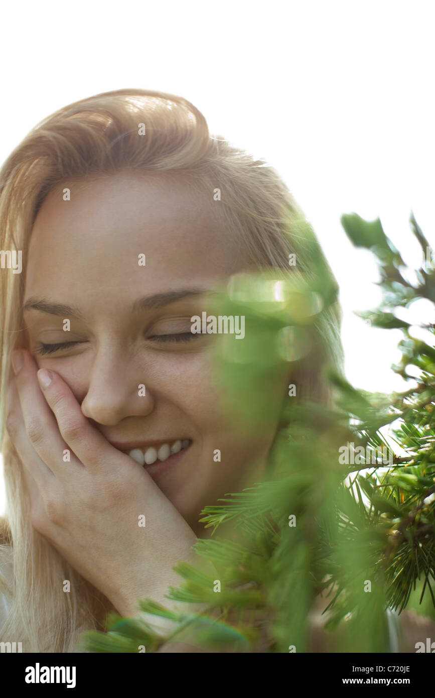 Young woman in nature, smiling with eyes closed - Stock Image