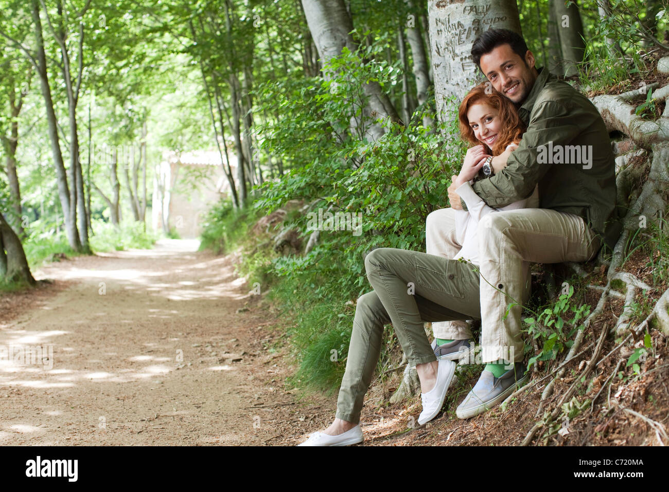 Couple sitting together beside wooded path, portrait - Stock Image
