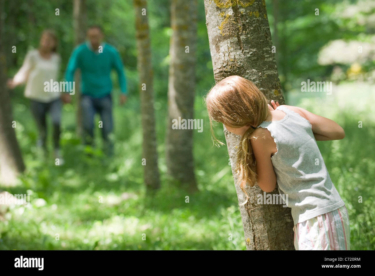 Girl hiding behind tree Stock Photo