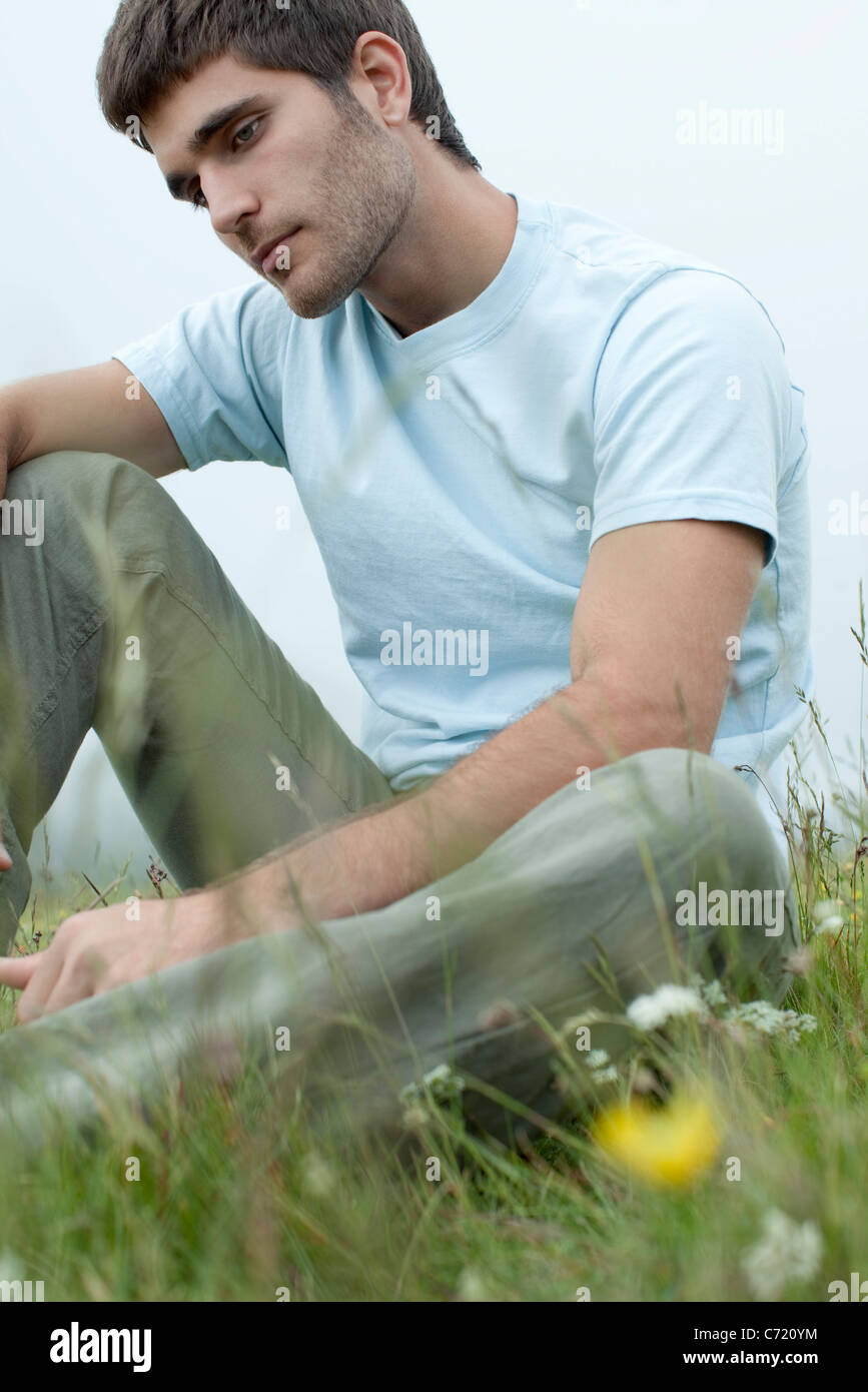 Man sitting on meadow in thought - Stock Image