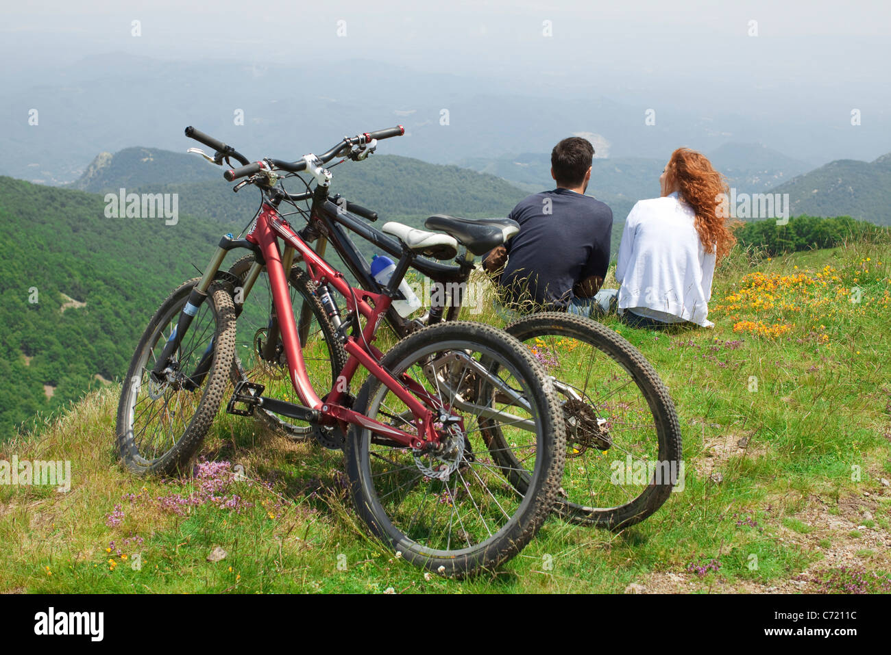 Couple sitting together on hill, looking at view, bicycles parked behind them - Stock Image