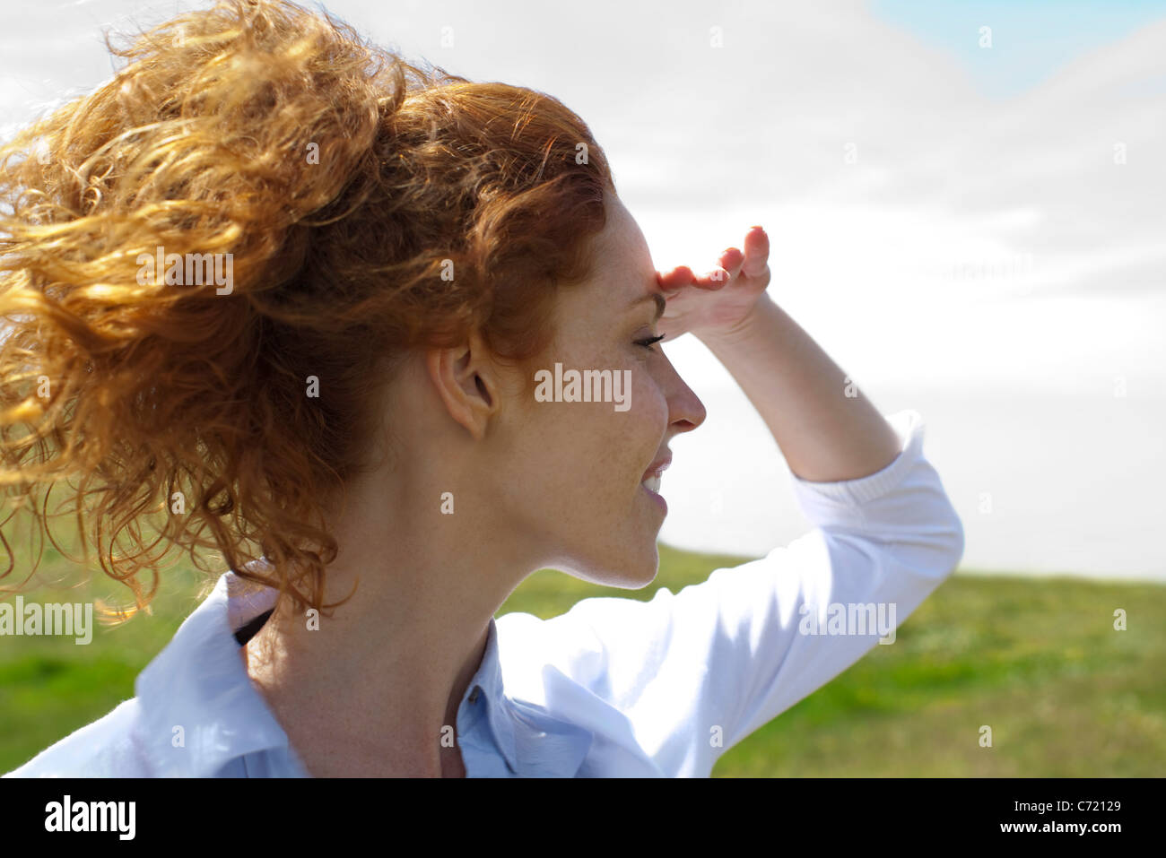Young woman looking into distance, hand shading eyes - Stock Image