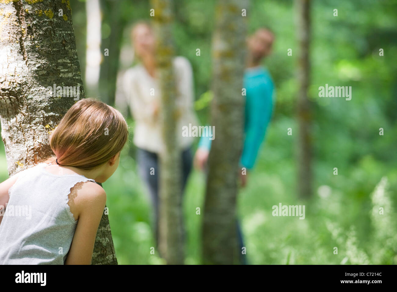 Girl hiding behind tree - Stock Image