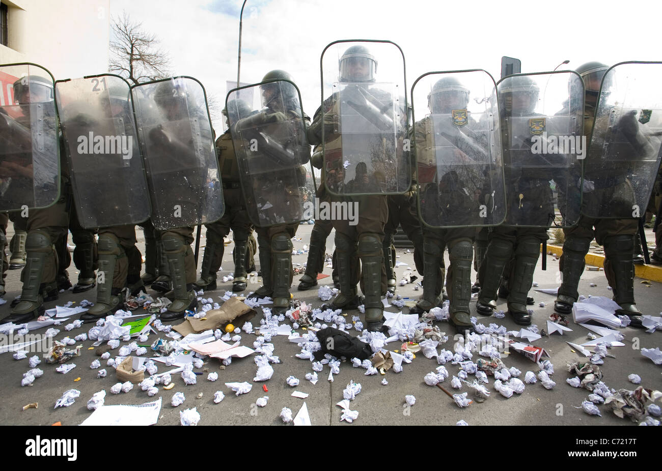 Line of Chilean police in full anti riot gear receiving paper balls from students protesting in Santiago de Chile - Stock Image