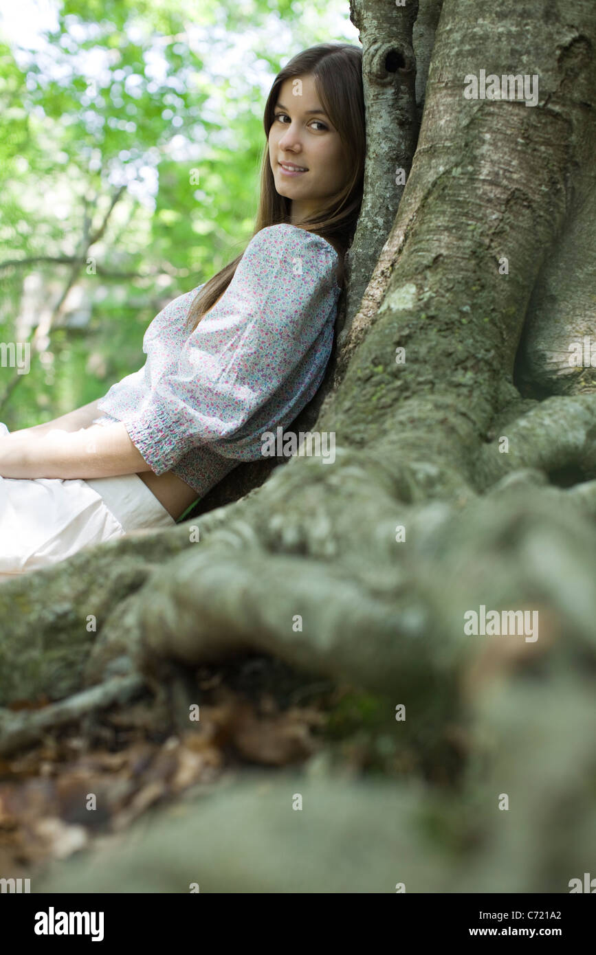Young woman leaning against tree - Stock Image