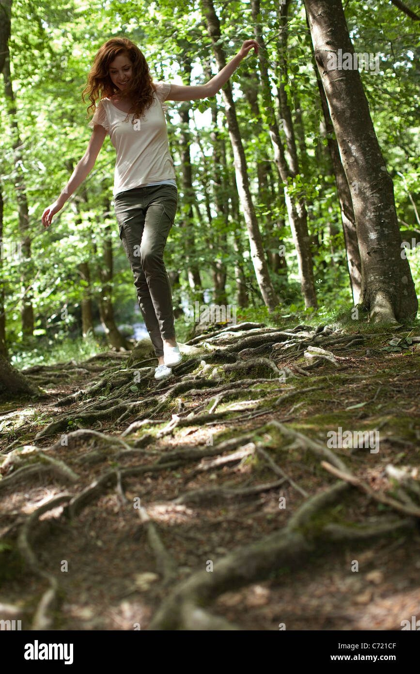 Woman walking on tree roots in woods - Stock Image