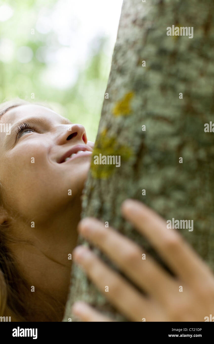 Young woman hugging tree, cropped - Stock Image