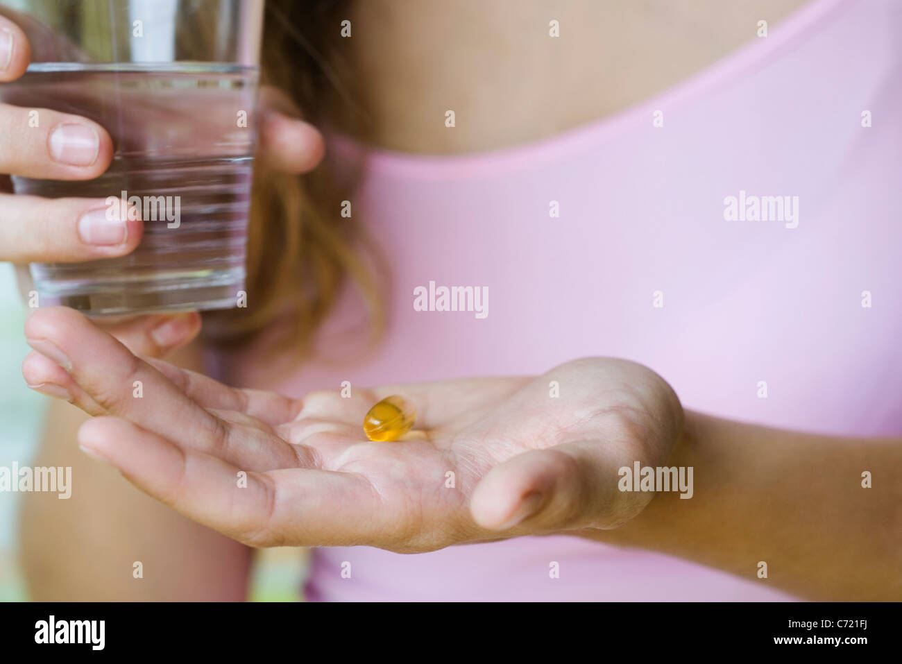 Young woman holding vitamin pill and glass of water, cropped Stock Photo