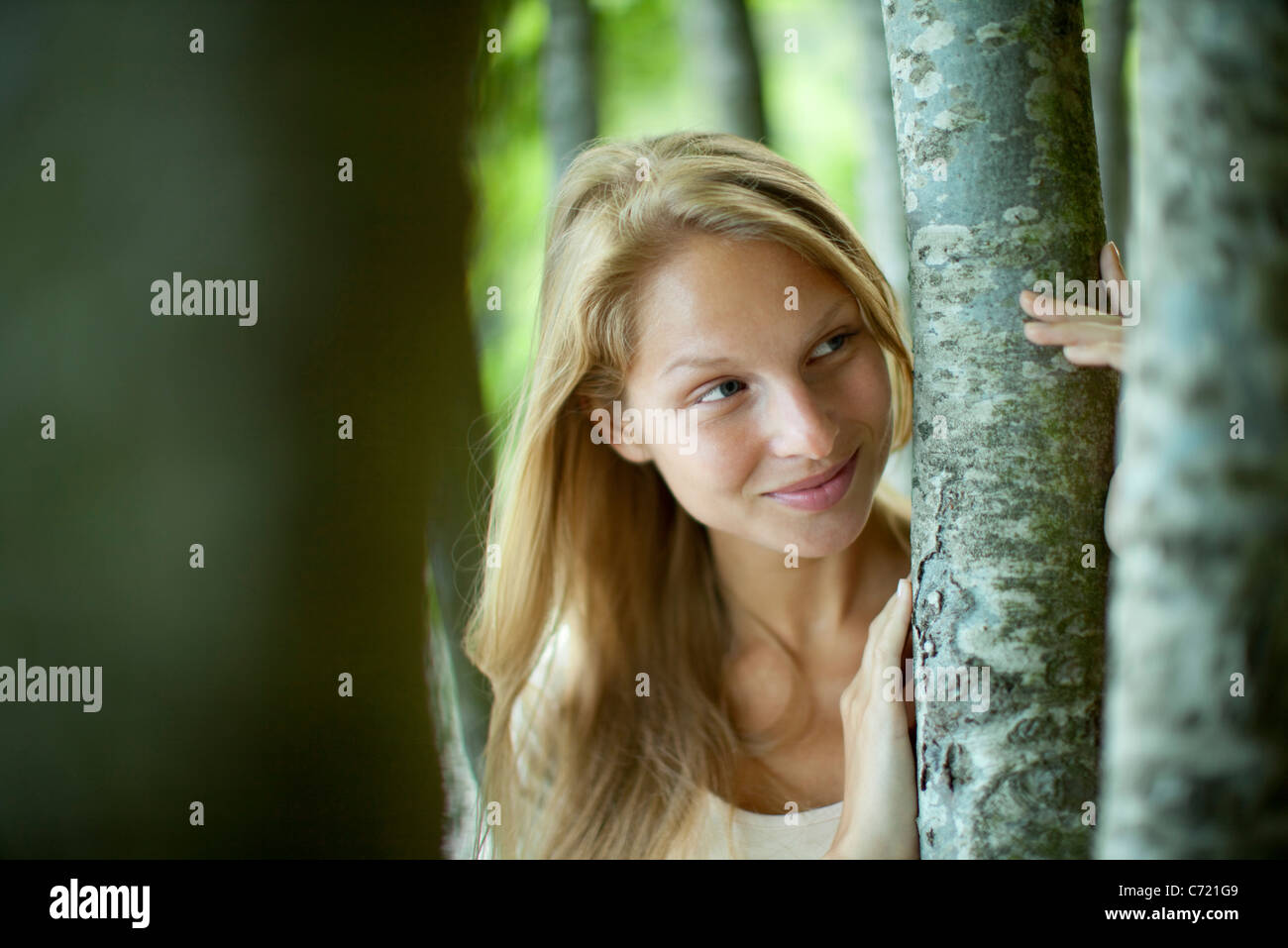 Young woman holding tree trunks - Stock Image