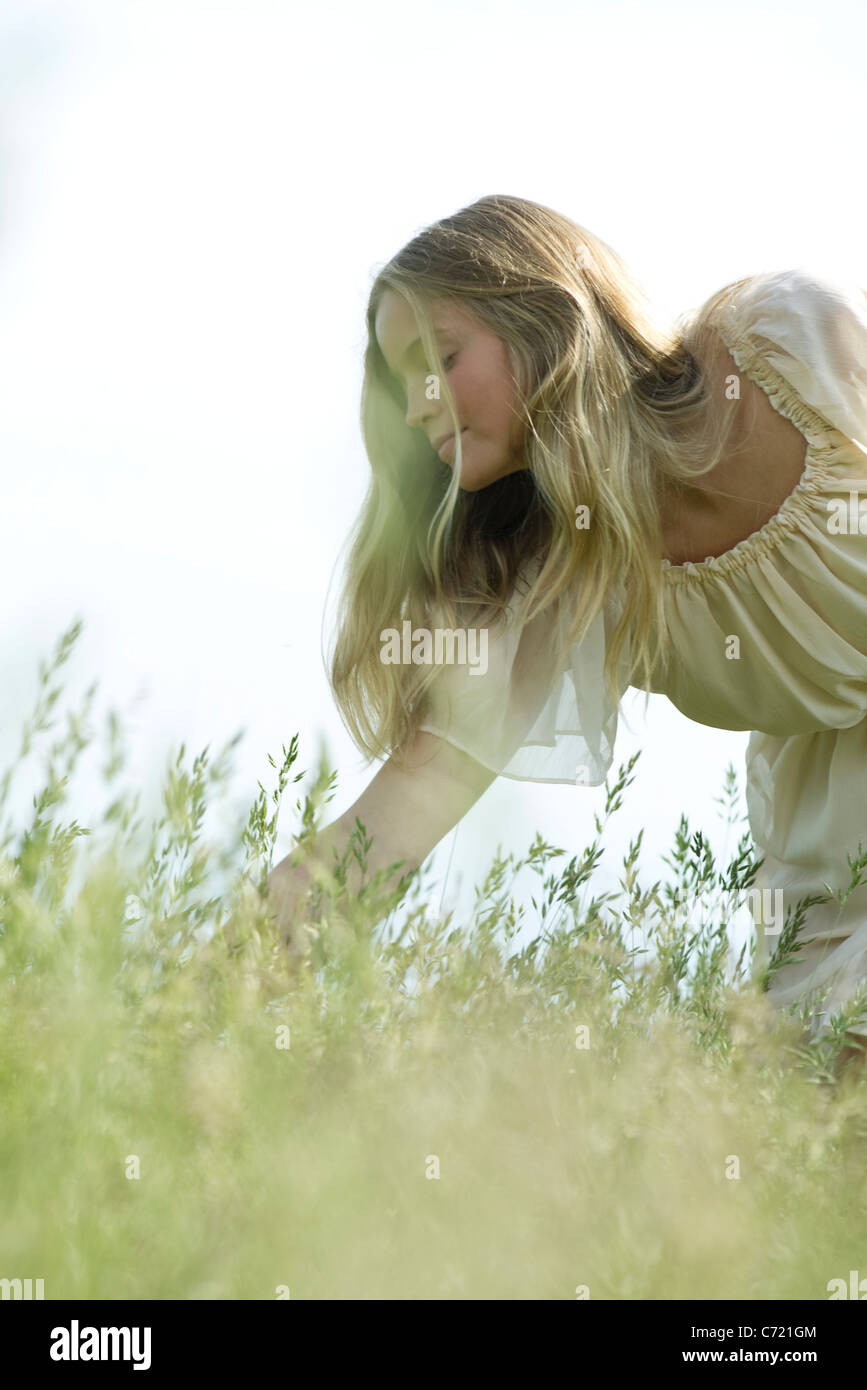 Young woman bending over tall grass - Stock Image