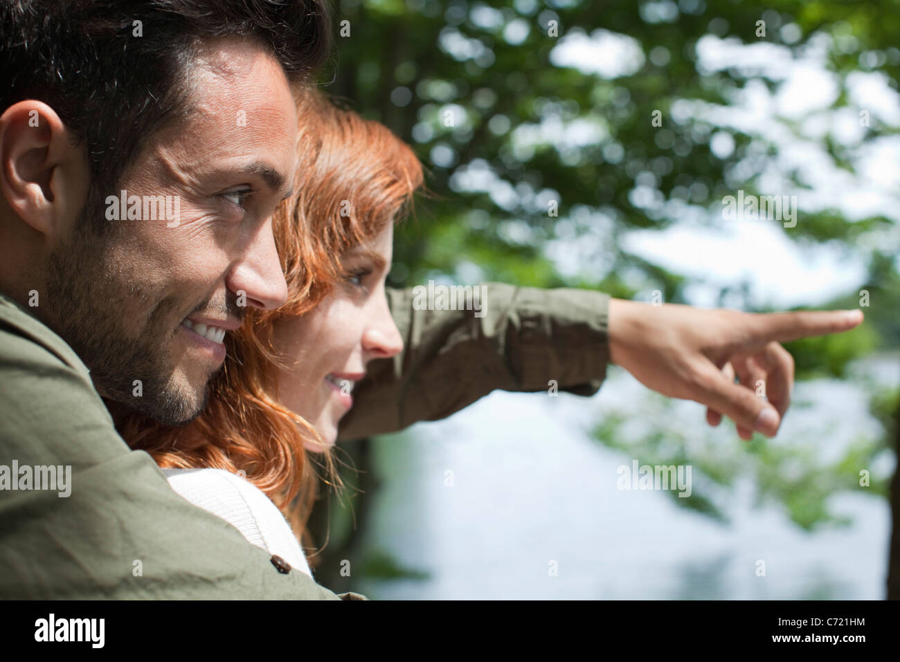 Couple together outdoors, looking at view - Stock Image