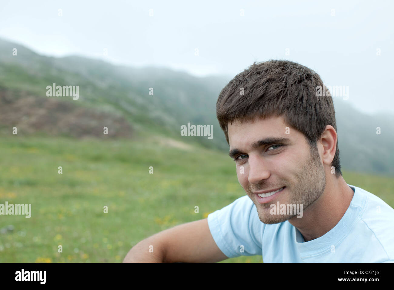 Man in nature, mountains in background, portrait - Stock Image