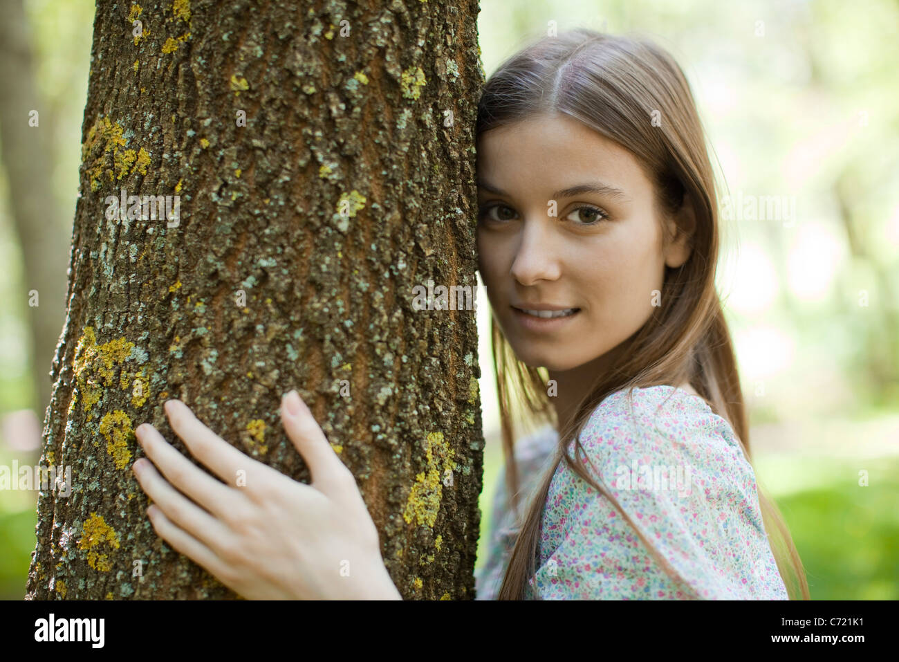Young woman hugging tree, portrait - Stock Image