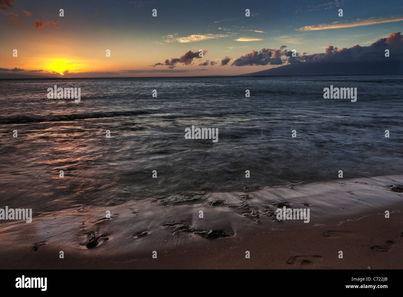 Sunset on a beach on Kaanapali Maui Hawaii showing the colorful sky colors with the island of Molokai in the distance Stock Photo