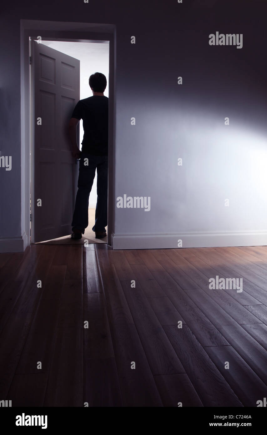 Back view of a shadowy male walking out of a dark room. - Stock Image