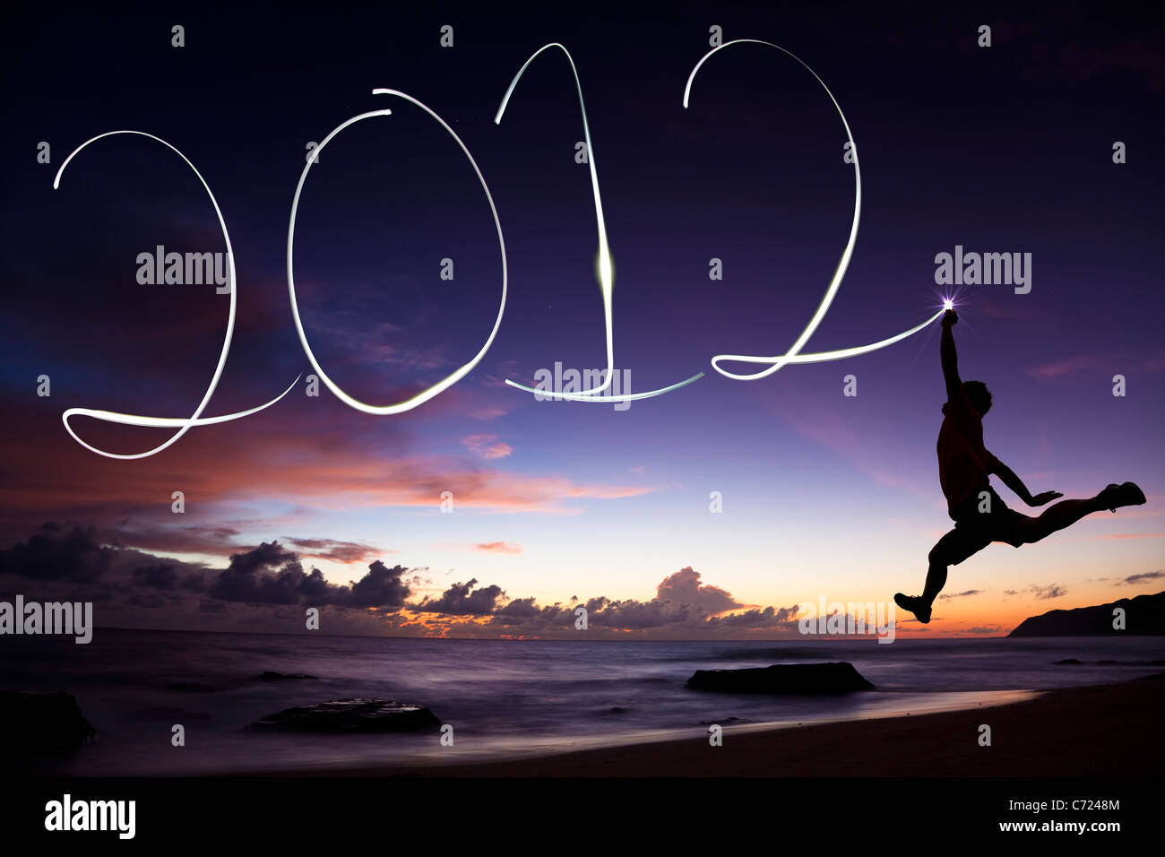 happy new year 2012. young man jumping and drawing 2012 by flashlight in the air on the beach before sunrise - Stock Image