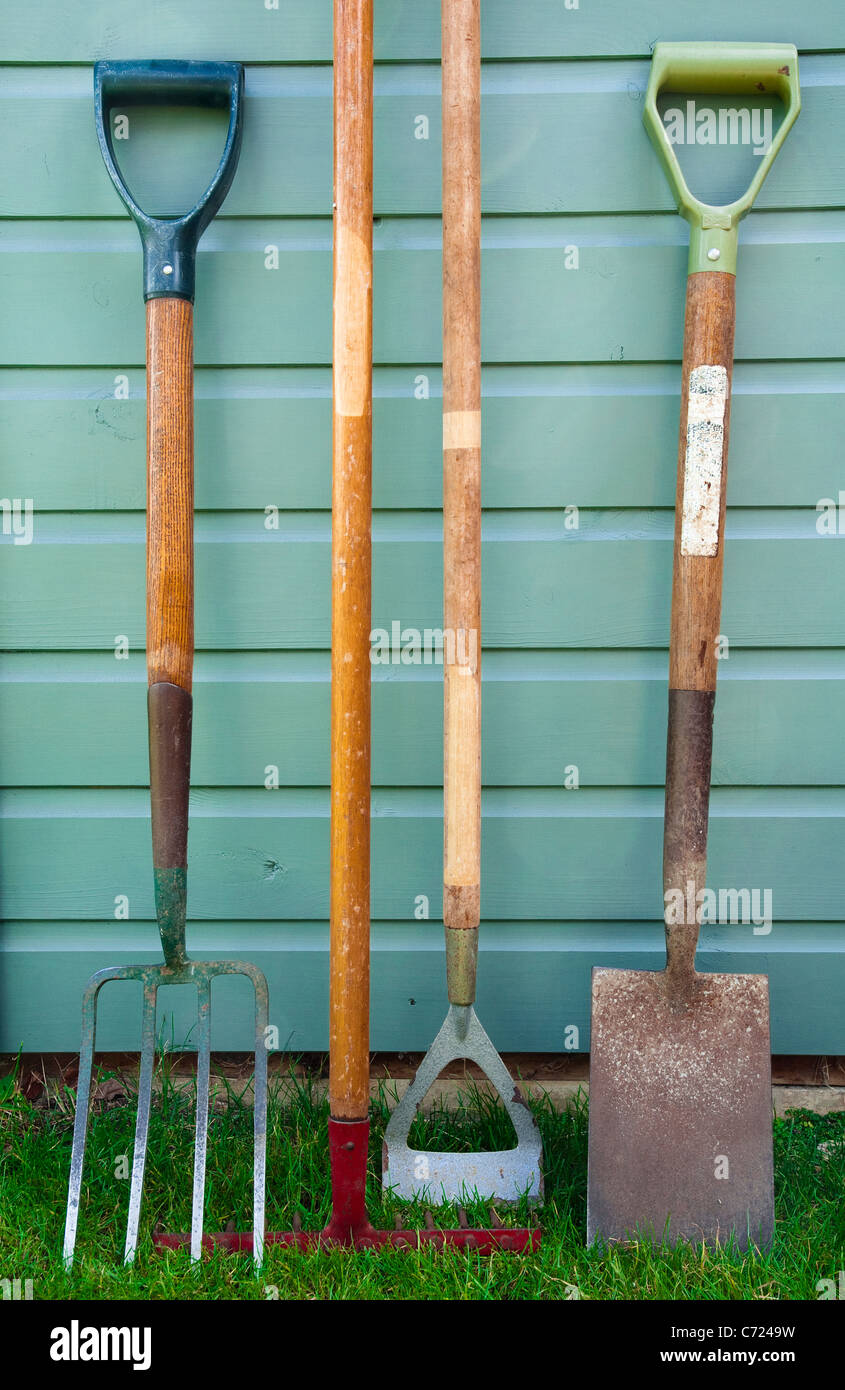 Well used garden/ gardening tools leaning against the side of a garden shed - including a  fork, rake, hoe and spade. - Stock Image