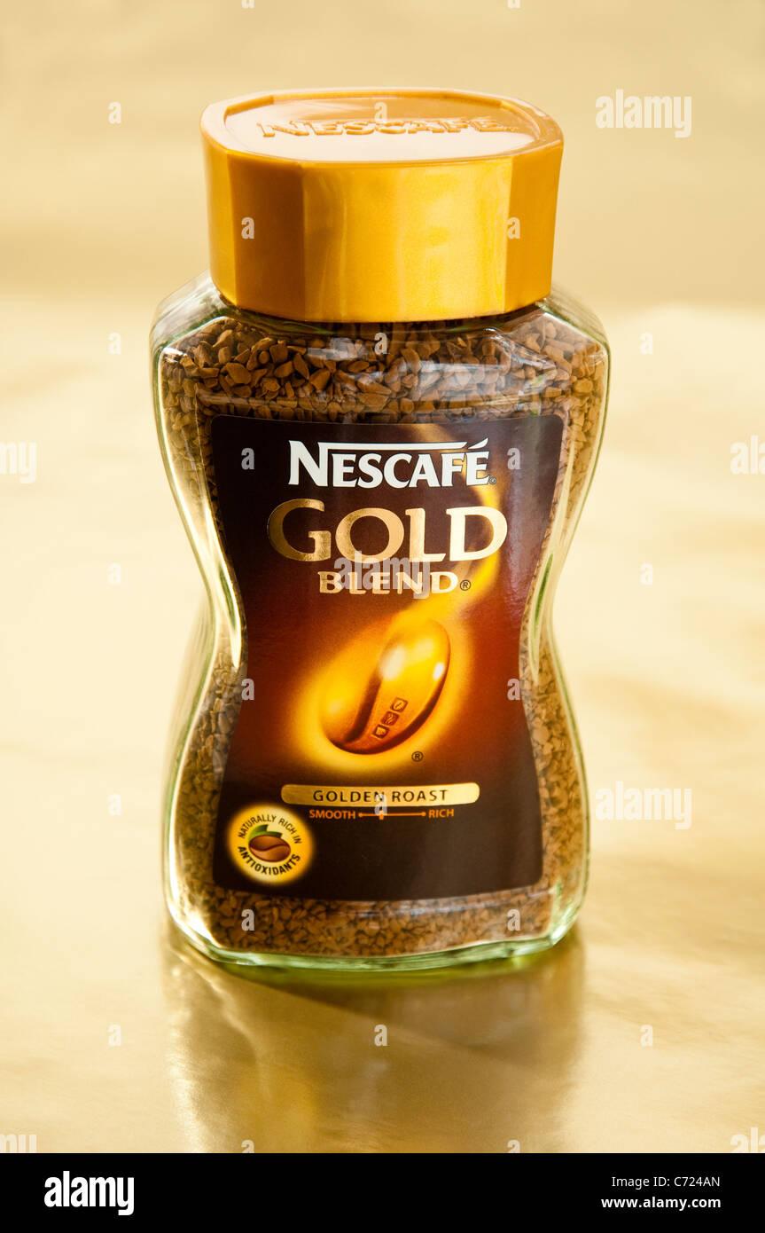Nescafe Gold Blend instant coffee jar on a soft golden background. - Stock Image