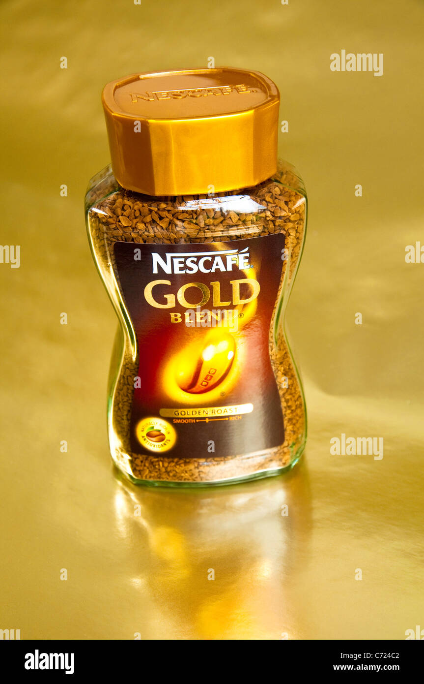 Nescafe Gold Blend instant coffee jar on a gold background. - Stock Image