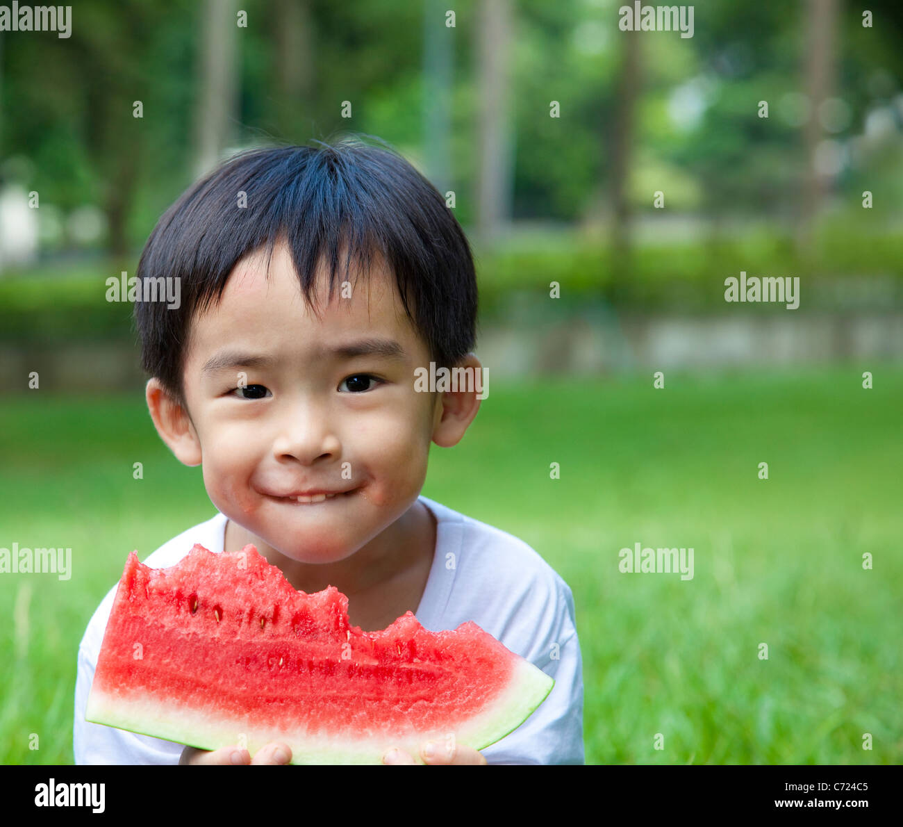 cute asian boy eating watermelon on the grass stock photo: 38770709