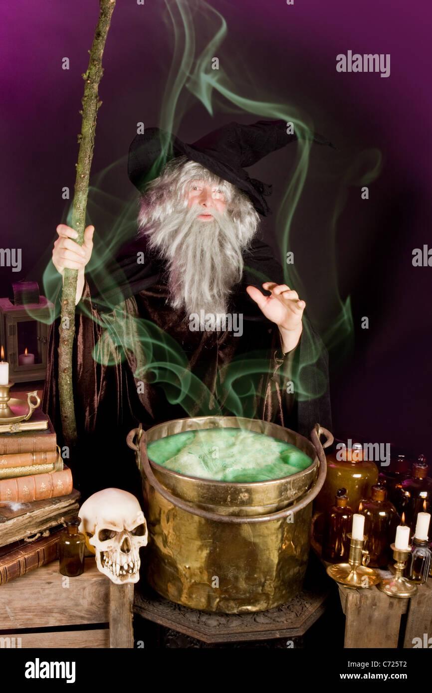 Evil sorcerer casting a spell on green poison soup - Stock Image