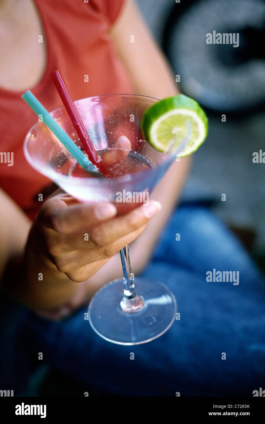 Young woman holding a cocktail glass. - Stock Image