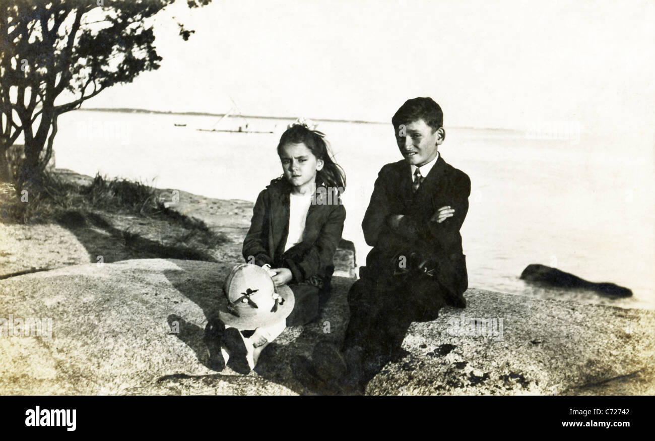 The photo, which dates to around 1921, shows a brother and sister on the rocks on Cape Cod, Massachusetts. - Stock Image