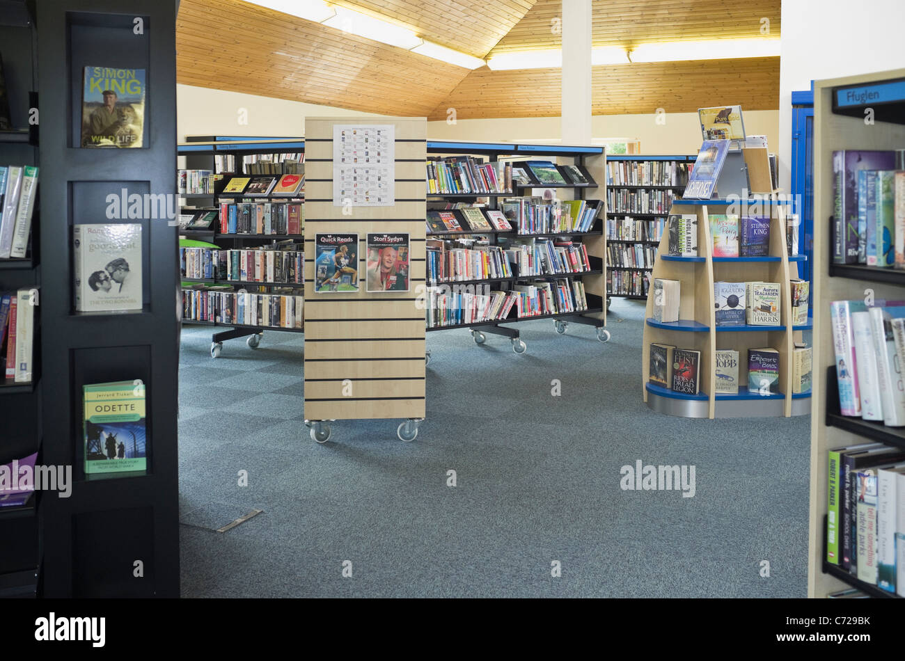 Inside a public library with books on book shelves. Wales, UK, Britain. - Stock Image