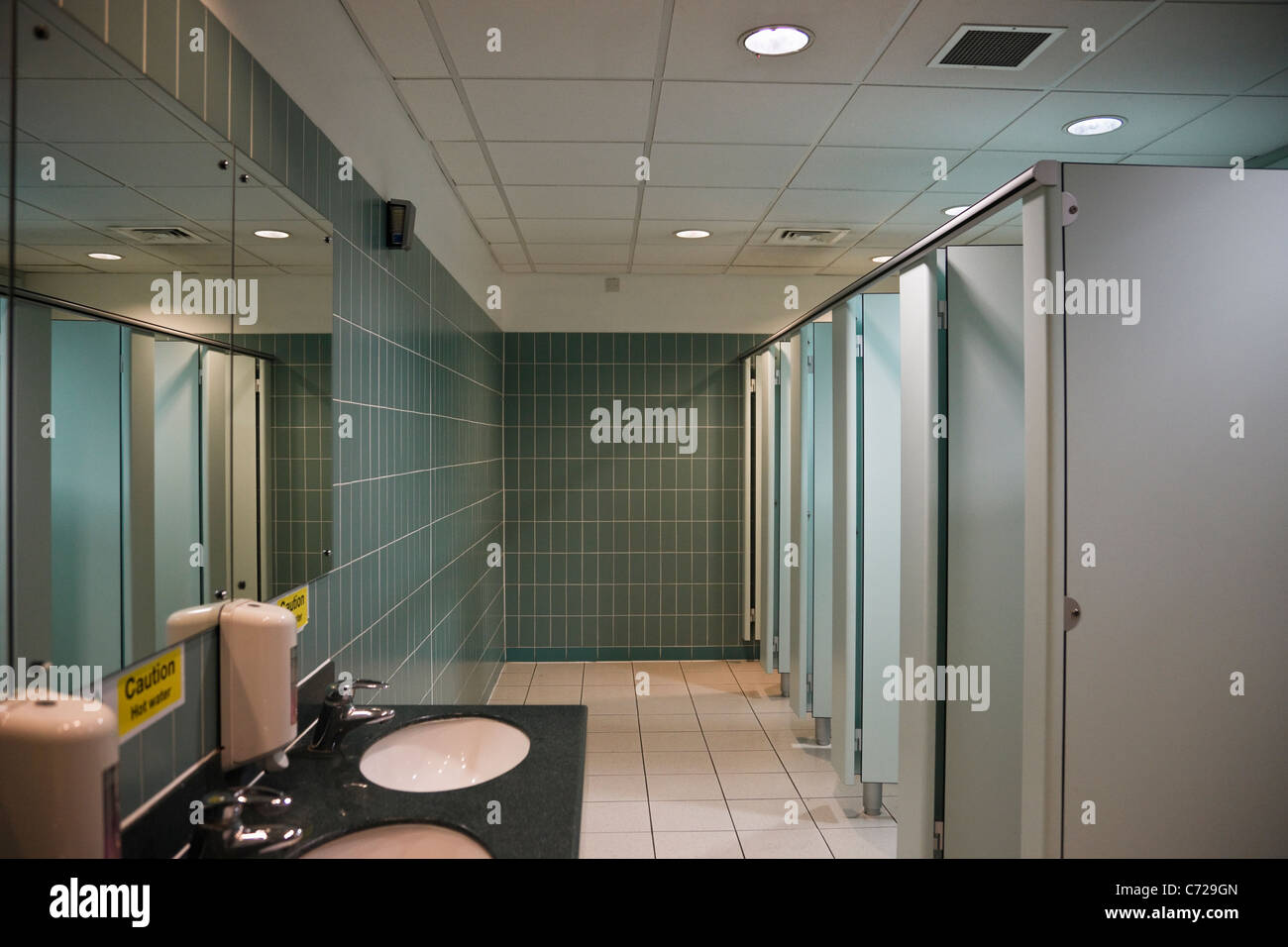 Clean modern public ladies' toilets with hand basins and toilet cubicles and tiled walls. England, UK, Britain - Stock Image