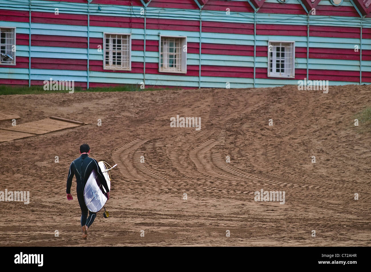 Surfer on the industrial beach of La Arena, Somosrrostro, Basque country, Euskadi, Spain. - Stock Image