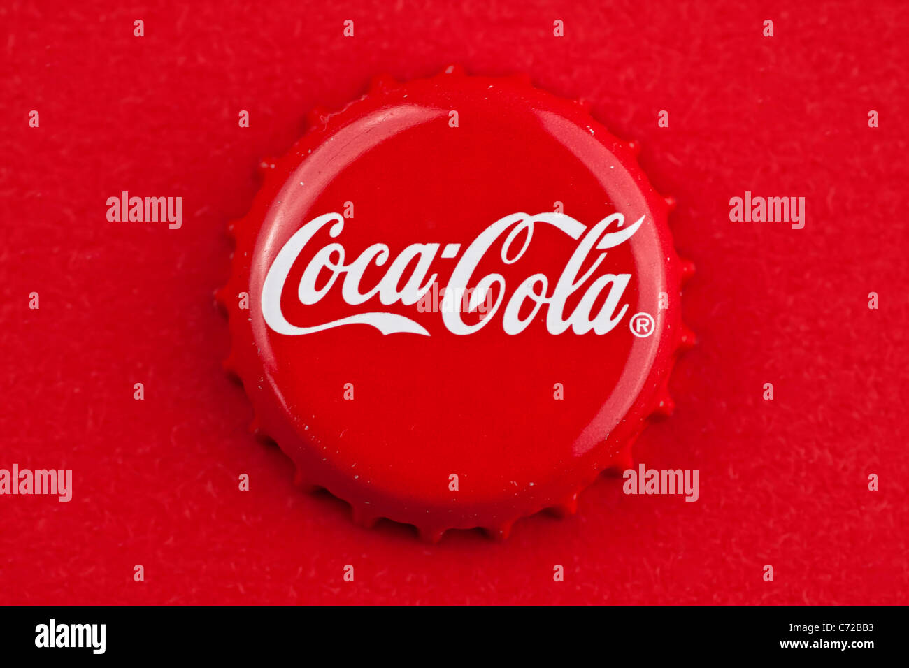 Muenster, Germany - September 10, 2011: Picture shows coca cola bottle cap on red background. - Stock Image