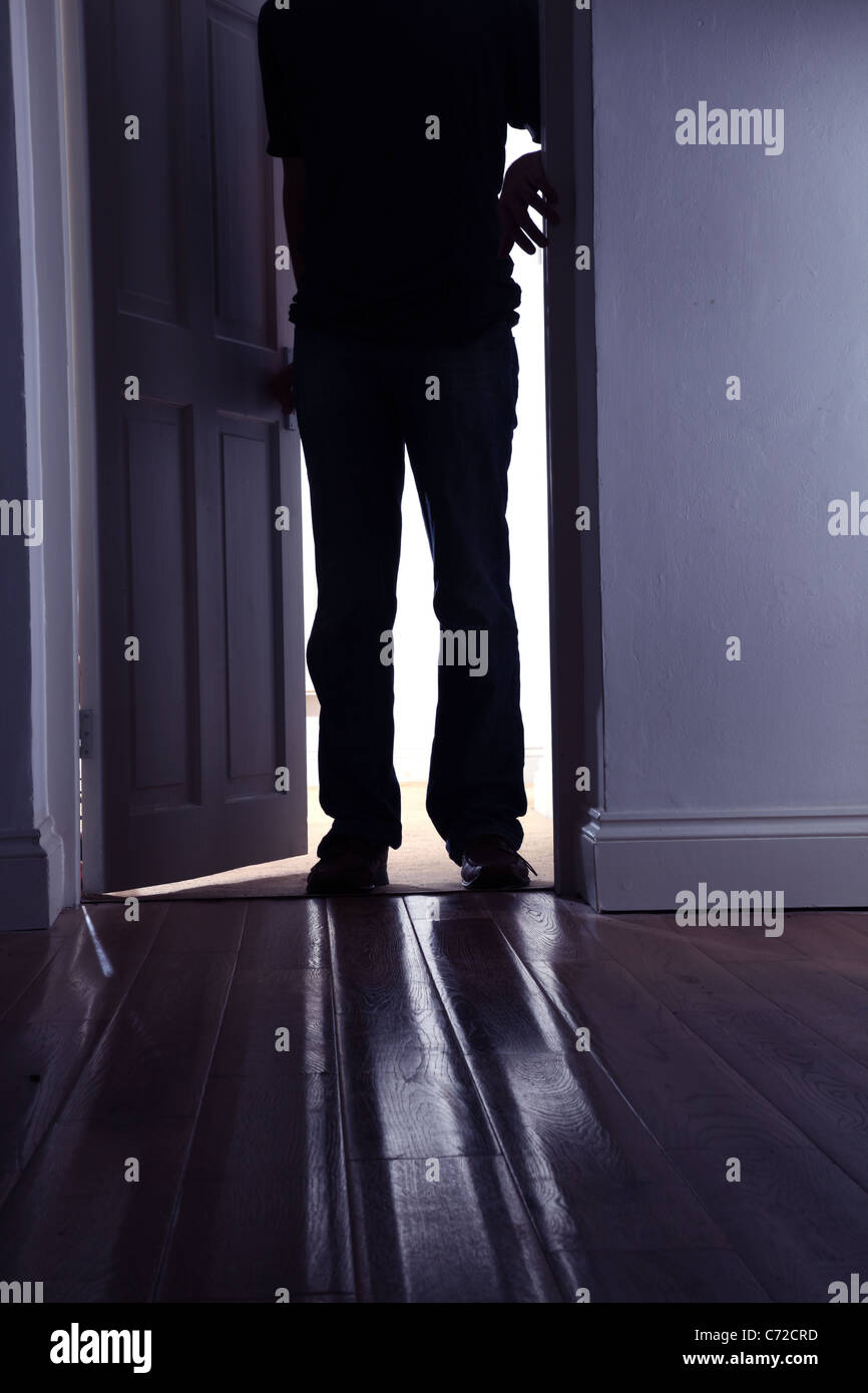 Male figure stepping into a dark room. - Stock Image
