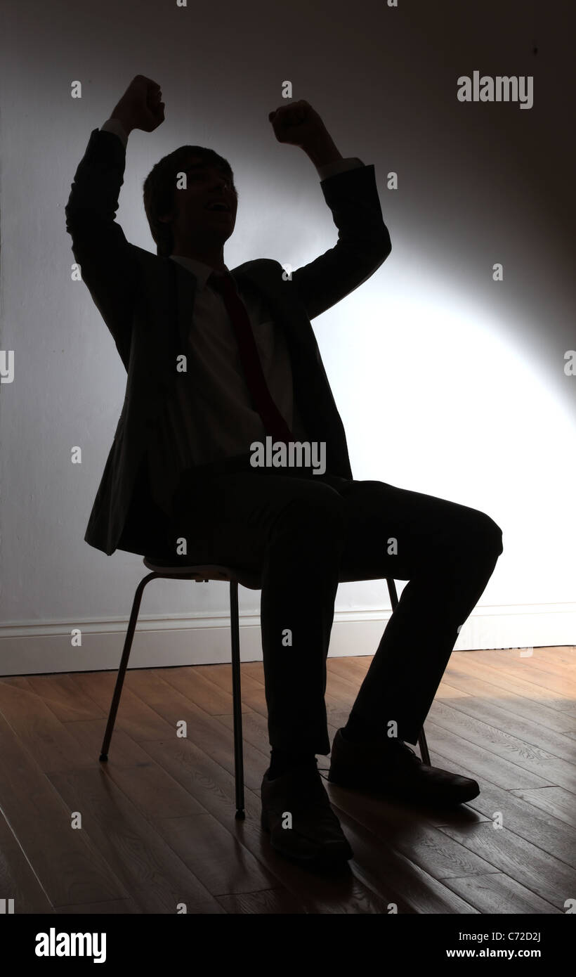 Silhouette of a young male sitting punching the air with his fists arms raised. - Stock Image