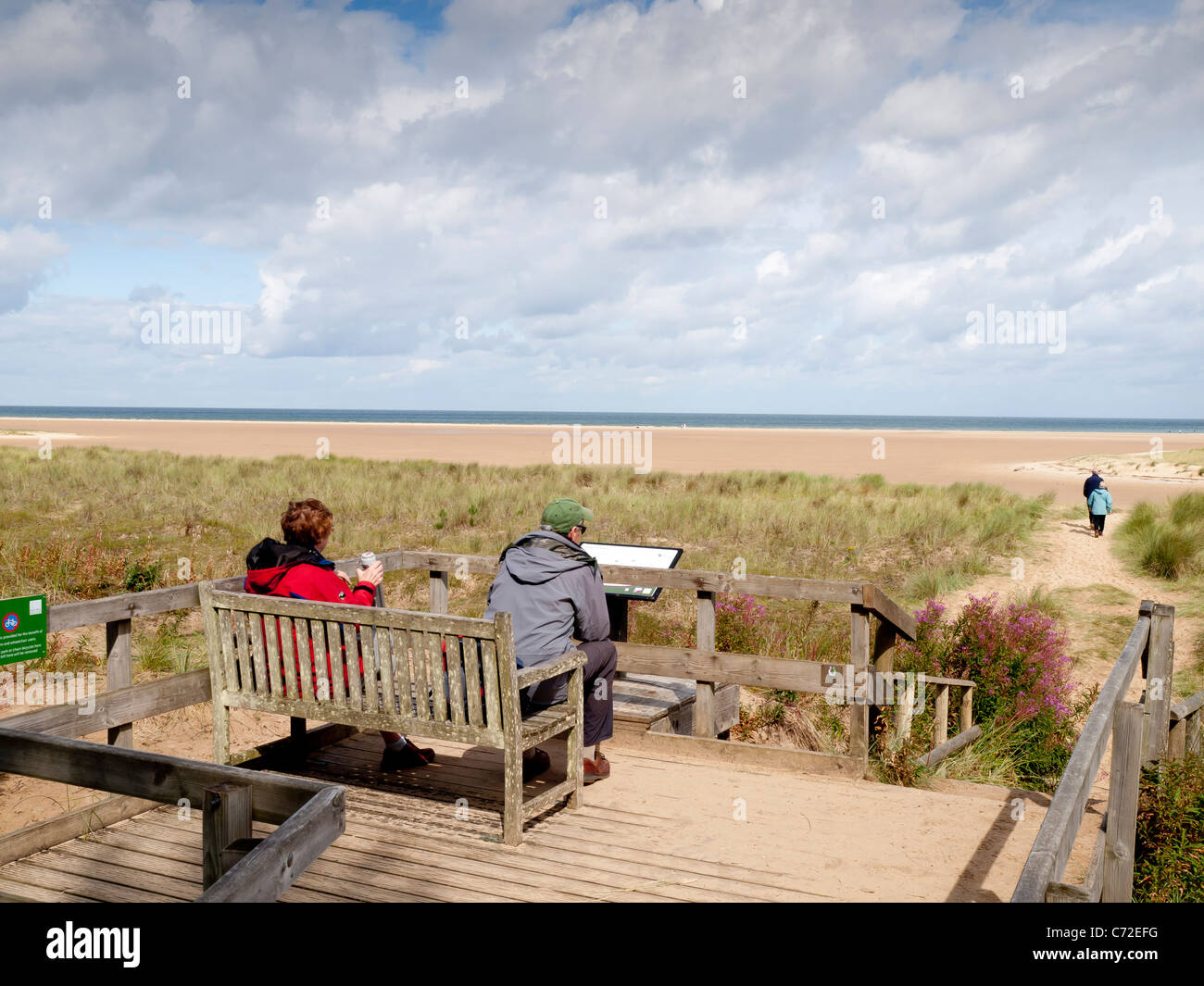 A couple rest on a bench at Holkham Beach look out point Norfolk UK - Stock Image