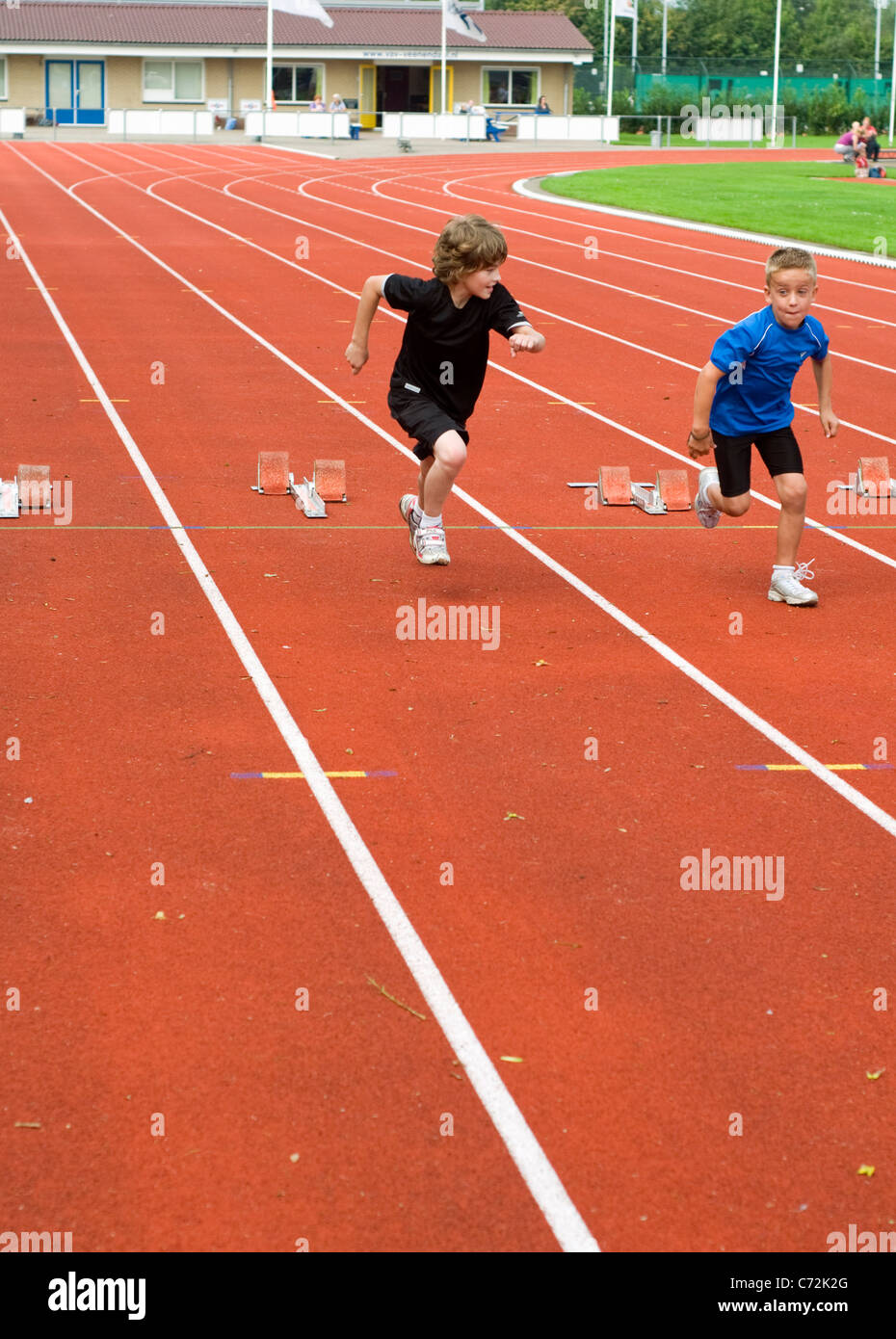 Two young boys taking part in a sprint race on an outdoor athletics track - Stock Image