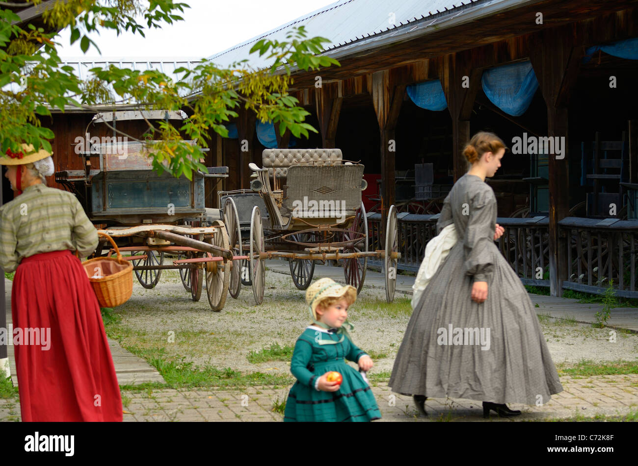 Three generations of women in period costumes at garage with carriages Country Heritage Park Milton Ontario - Stock Image
