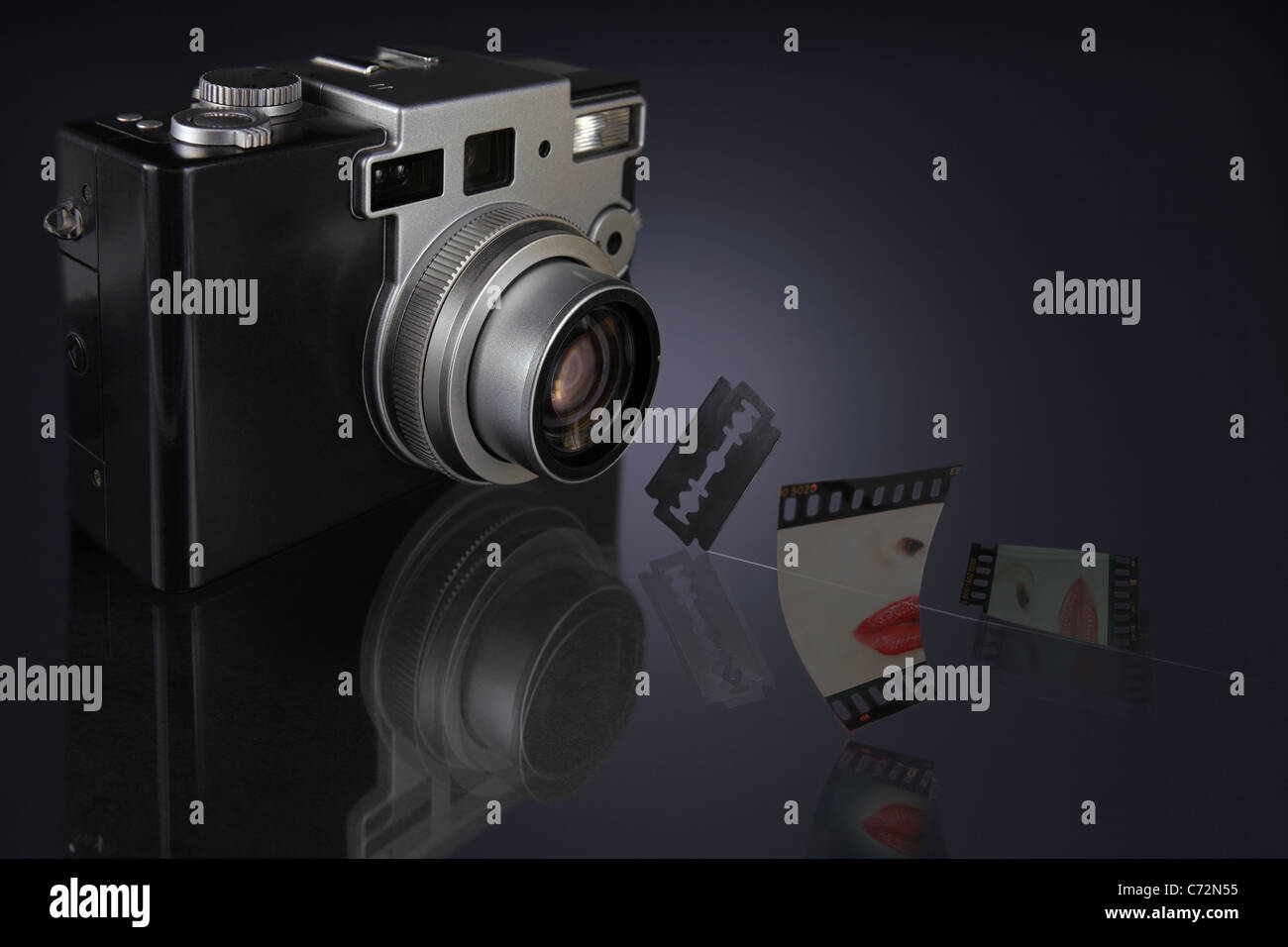 camera with lens focused on razor blade hanging in mid air and a slide cut sharply into two pieces - Stock Image