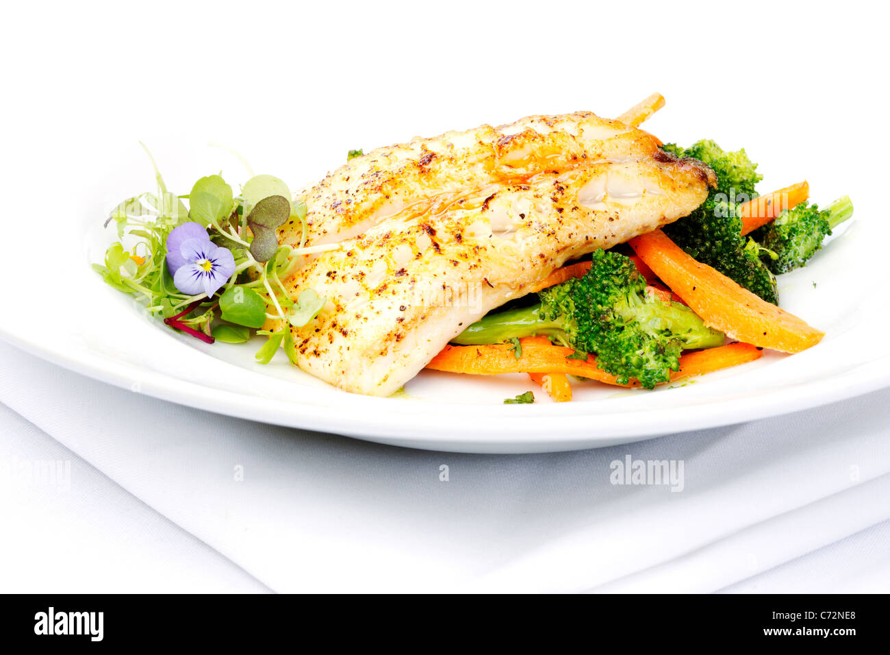 Fresh black cod on bed of broccoli and carrots with a touch of micro herbs - Stock Image