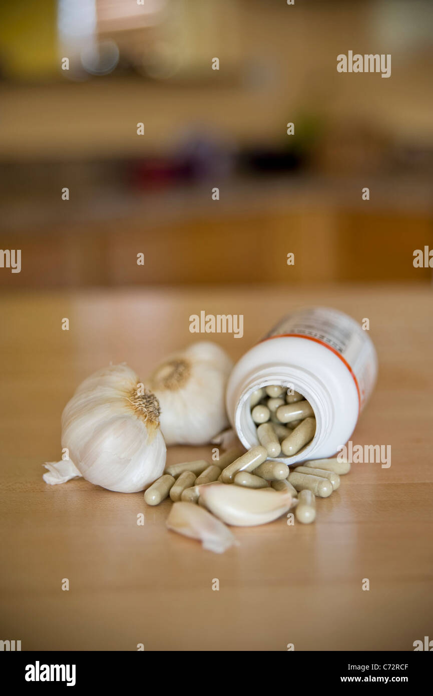 Aged Garlic capsules - in a still life arrangement with garlic cloves Stock Photo