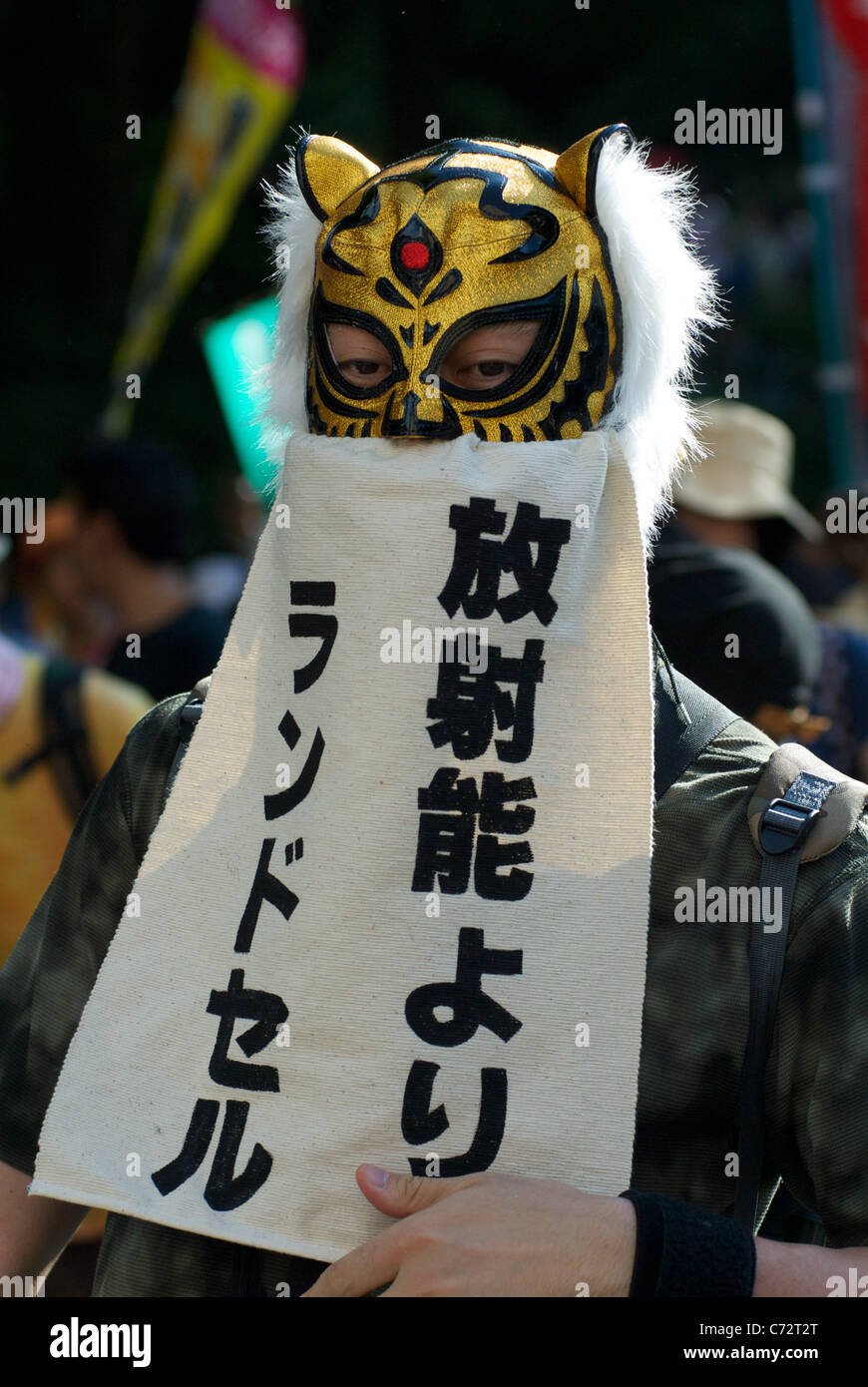 An Anti-Nuclear protester in a tiger mask attends a rally at an Anti-Nuclear protest on the 6 month anniversary - Stock Image