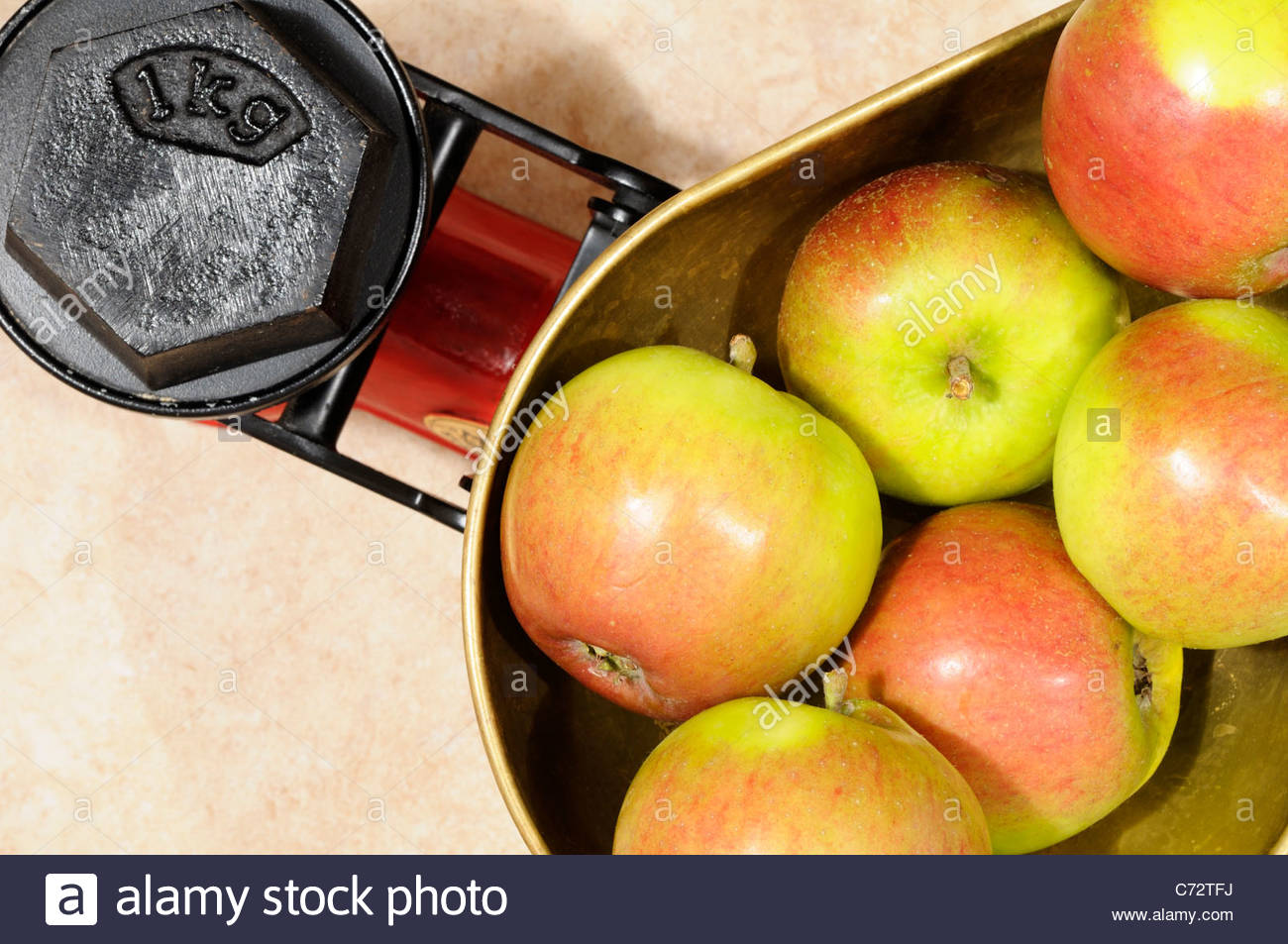 Apples on Kitchen scales 1kg, England - Stock Image