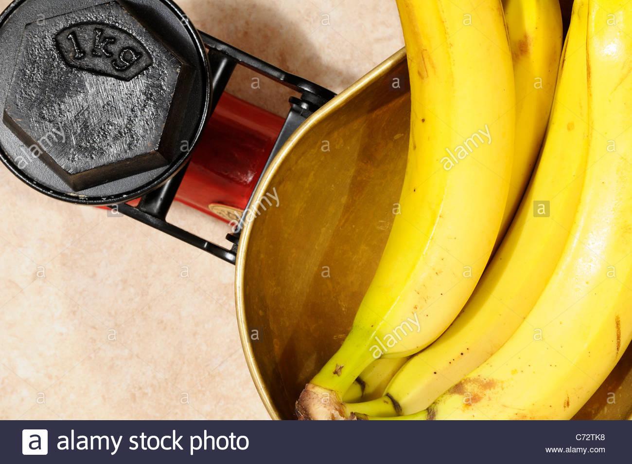 Bananas on Kitchen scales 1kg, England - Stock Image