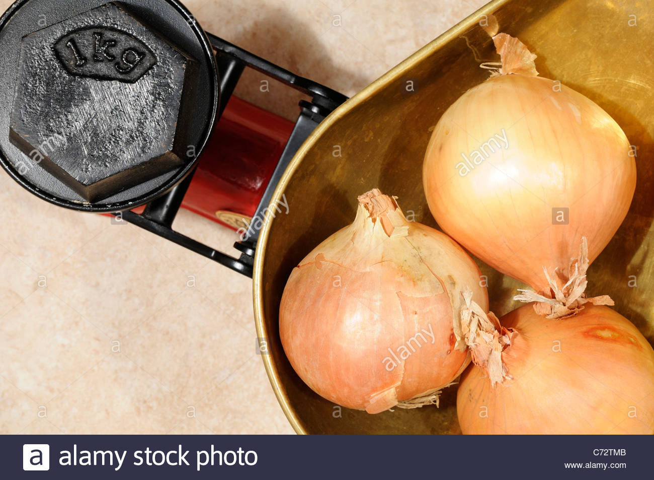 Onions on Kitchen scales 1kg, England Stock Photo