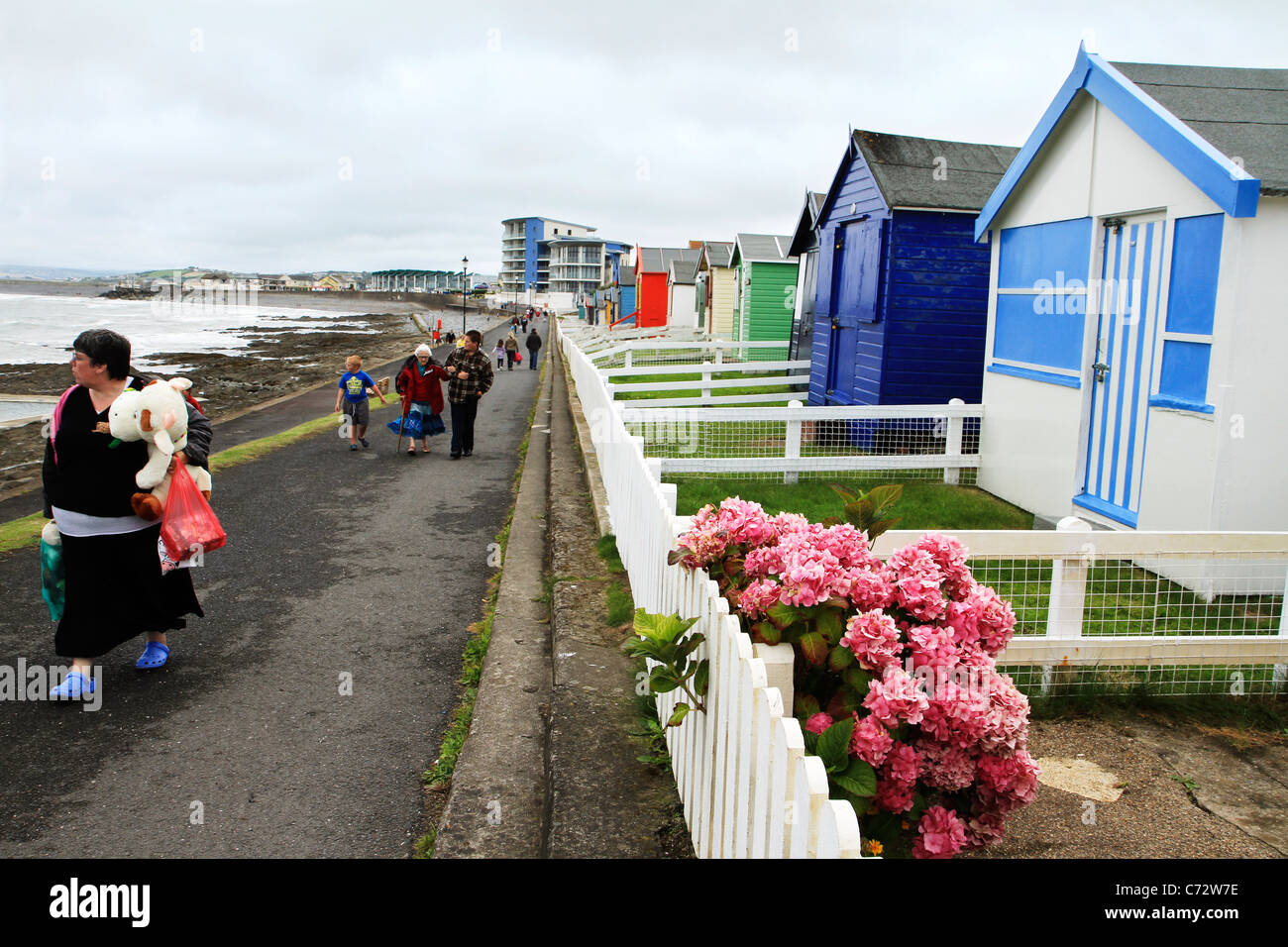 Holidaymakers and Beach Huts on seafront at Westward Ho!, North Devon UK - Stock Image